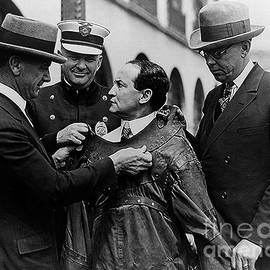 Harry Houdini being fitted into a straitjacket - American School