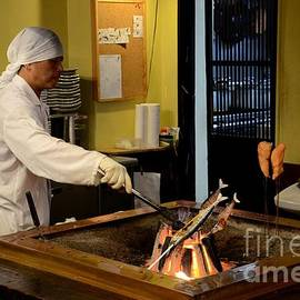 Imran Ahmed - Japanese chef in kitchen grills fish on indoor coal fire Tokyo Japan