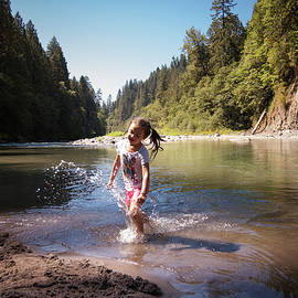 Little girl playing in river running through forest by Bradley Hebdon