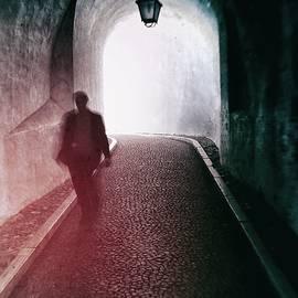 Carlos Caetano - Man walking through a tunnel