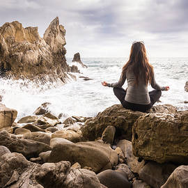 Bradley Hebdon - Meditating woman on rocky beach
