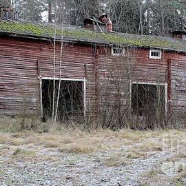 Old farm machinery barn in by Esko Lindell