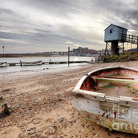 Old rowing boat and lookout tower on beach by Simon Bratt Photography LRPS