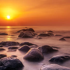 Orange sunset long exposure over sea and rocks by Sandra Rugina