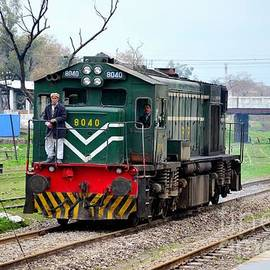 Imran Ahmed - Pakistan Railways locomotive engine passes Peshawar station as small child watches