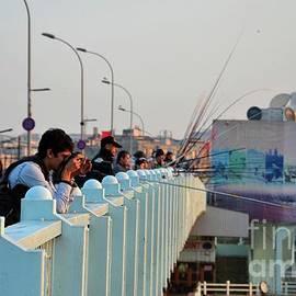 Imran Ahmed - Photographer and people fishing from bridge crossing Bosphorus sea Istanbul Turkey