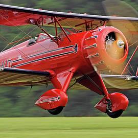 Red WACO YMF-5 on a green grass strip by Rodman Reilly