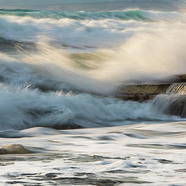 Rocky seashore, wavy ocean and wind waves crashing on the rocks by Michalakis Ppalis