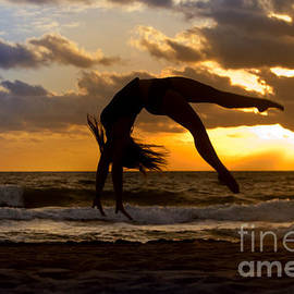Anthony Totah - Silhouette of woman doing a back flip on a beach
