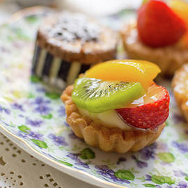 Bradley Hebdon - Small fruit tarts laid out on an antique china plate