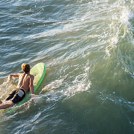 Bradley Hebdon - Surfer paddles out on surfboard without a wetsuit