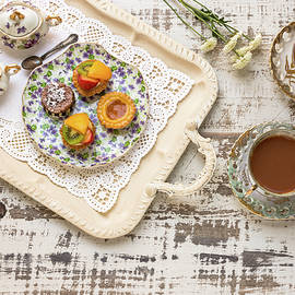 Bradley Hebdon - Tea cups and fruit tarts laid out on rustic table