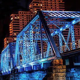 Randall Nyhof - The Blue Walking Bridge from the River Bank Below at Night