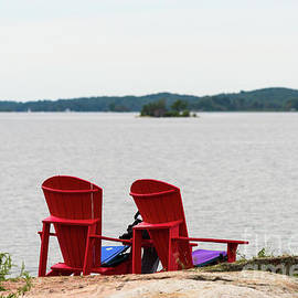 Two Red Chairs At A Lake by Les Palenik