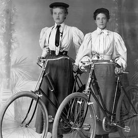 Two Young Ladies With Their Bicycles Circa 1895 by Anthony Murphy