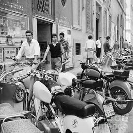 Various scooters, including Lambretta and Vespa, parked on a str - The Harrington Collection