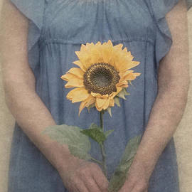 Woman In Blue Dress Holding Sunflower by Clayton Bastiani
