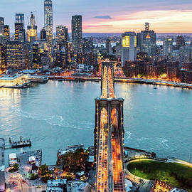 Aerial Of New York City And Brooklyn Bridge At Dusk by Matteo Colombo