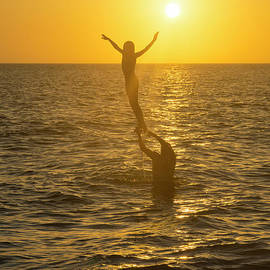 A father lifts his daughter out of the water along the beach at