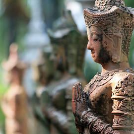 A Line of Praying Buddha Statues, Chiang Mai, Thailand by Derrick Neill