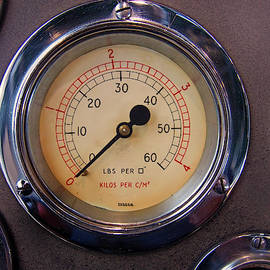 a round metal pressure gauges with a shiny chrome surrounds by Philip Openshaw