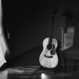 Tennessee Witney - Acoustic Spanish guitar on a stand in the moody shadows of a dark room with light from a curtain