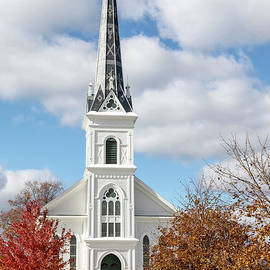 Charming white church and steeple on autumn day, against blue sk by Craig Sterken