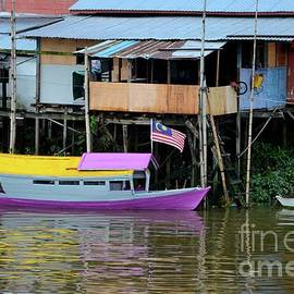 Colorful purple  and yellow boat on Sarawak River by kampong village Kuching Malaysia by Imran Ahmed