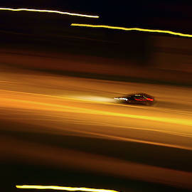 Fast car driving on a night street. Blurred motion by Andrei Kuznetsov