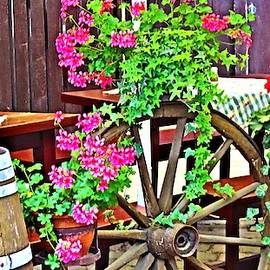 German barrows, old wooden wheel and geraniums  by Victoria Beasley