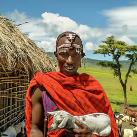 Maasai tribesman holding Goat by Amyn Nasser Photographer - Neptune