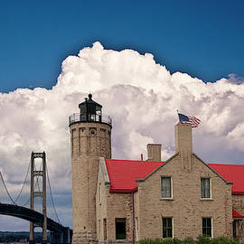 Mackinac Bridge and the Mackinaw City Lighthouse at the Straits of Mackinac in Michigan by Randall Nyhof