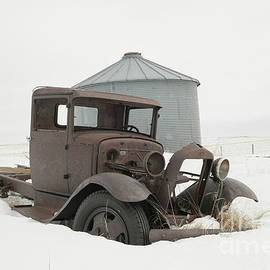 Old truck and grain silo on a gray winter day by Jeff Swan