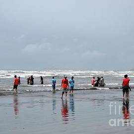 People And Families Wade In Water And Enjoy The Waves At Sea View Beach Karachi Pakistan by Imran Ahmed