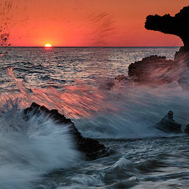 Red sun through the waves. Roche reefs at sunset.  by Guido Montanes Castillo