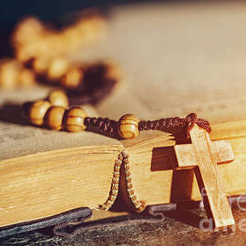 Rosary With Cross Laying On A Bible Book. by Michal Bednarek