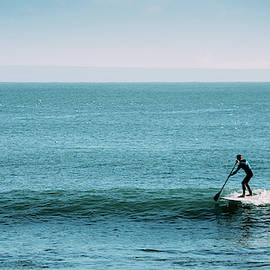 Silhouette Of Unidentifiable Man Catching A Wave While On A Stand Up Paddle Board by Alexandre Rotenberg