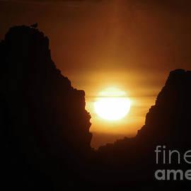 Sunset between two rocks by Jeff Swan