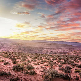 Sunset on desert landscape with a natural bridge in Southern Utah by Rod Gimenez