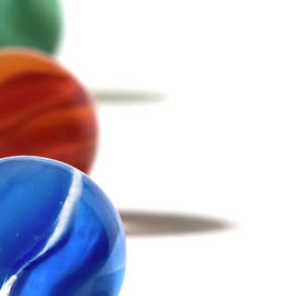 Three Different Colored Marbles Aligned by Daryl Solomon