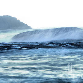 Wave overwhelming a smooth Rock by Jeff Swan