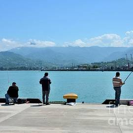 Fishermen with fishing rods at the Black Sea pier Batumi harbor Georgia by Imran Ahmed