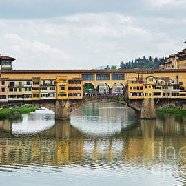 Ponte Vecchio. View of the historic buildings in Florence. Reflection in the river. by Beautiful Things