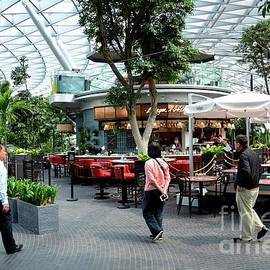 Visitors walk near a cafe inside the Jewel attraction at Singapore's Changi Airport by Imran Ahmed