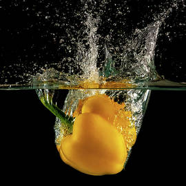 Yellow bell pepper dropped and slashing on water by Michalakis Ppalis