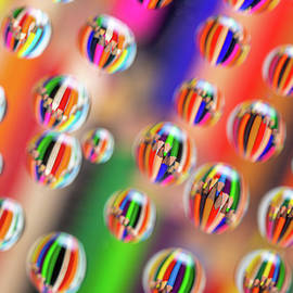 Drawing pencils reflected on waterdrops resting a piece of glass by Michalakis Ppalis