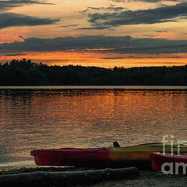 A pair of canoes at sunset by Claudia M Photography