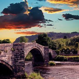 A Sunset, Pont Fawr and Tu Hwnt Ir Bont Tearoom, Llanrwst, Wales by Derrick Neill