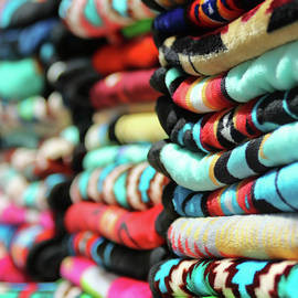 An Assortment of Colorful Stacked Blankets Arranged in a Row by Derrick Neill