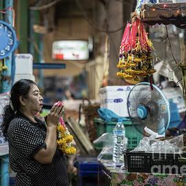 Bangkok Market vendor praying by Tony Camacho